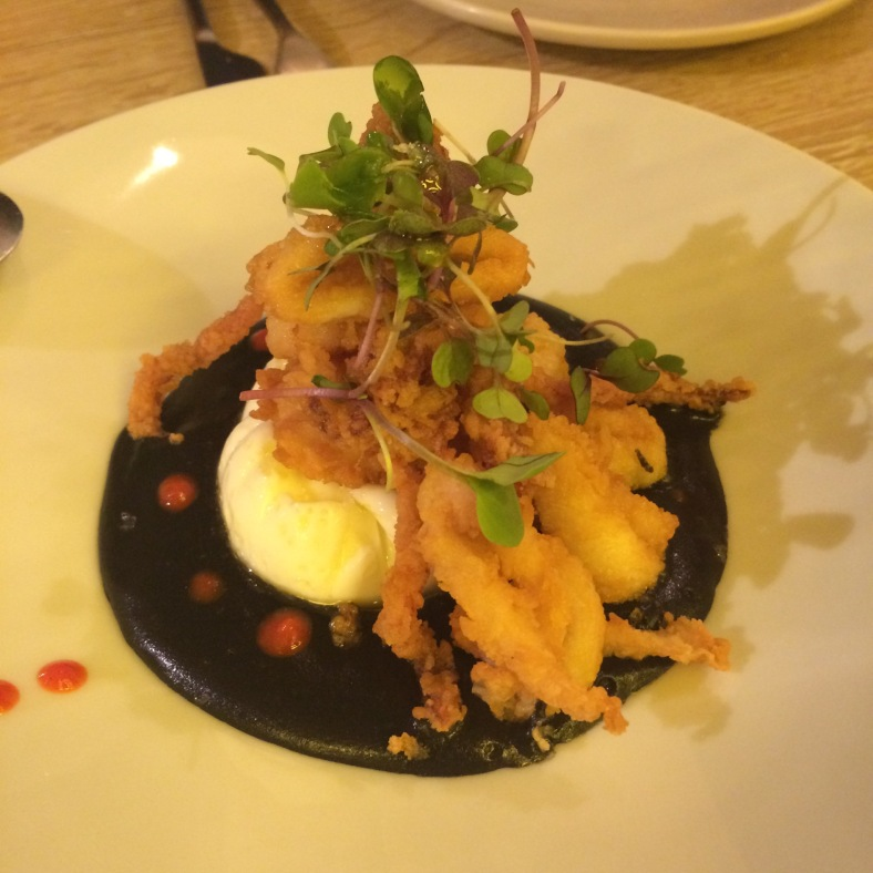 Cremoso de patata de tinta de calamar, huevo poché y patitas de chipirón