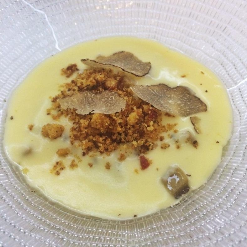 huevo de corral con crema de patata ligeramente ahumada, migas crujientes y trufa negra
