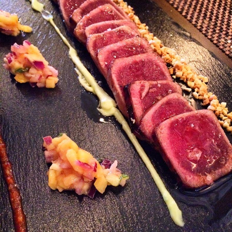 Tataki de atún almendrado acompañado de tartar de mango, mayonesa de wasabi y kimchi