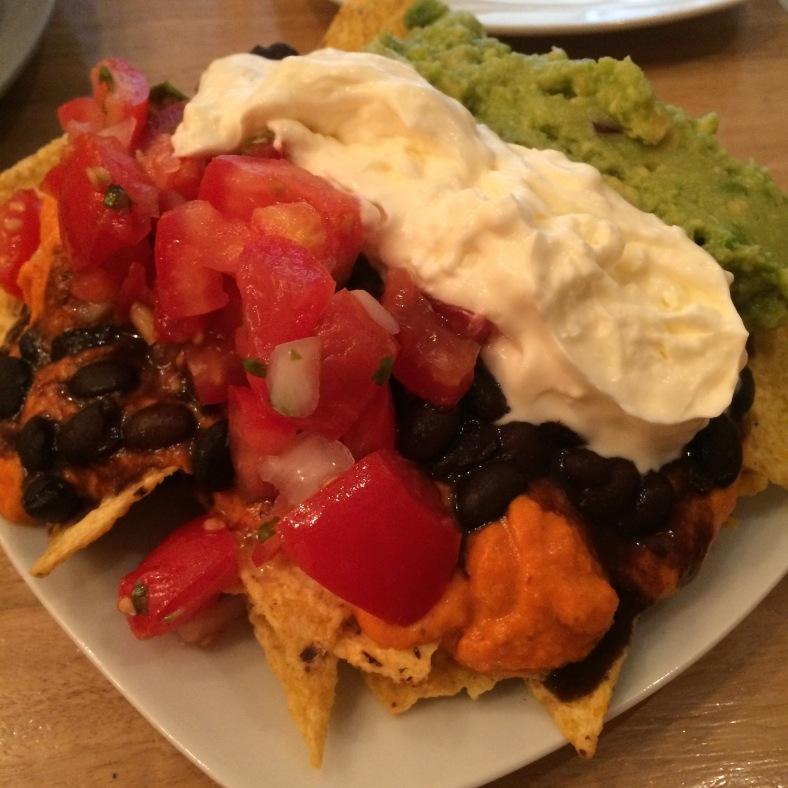 Nachos con guacamole, crema agria, frijoles, pico de gallo y salsa de cheddar