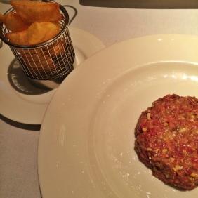Steak tartar con patatas souflé y helado de mostaza